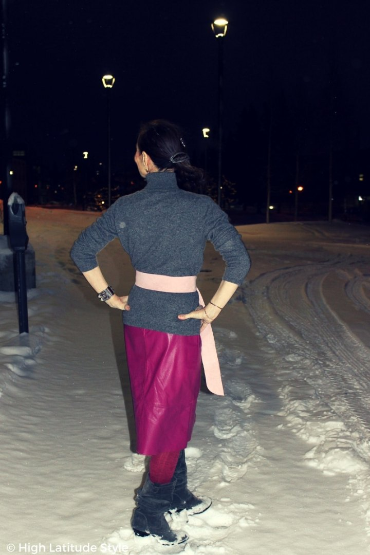 Back view of Alaskan woman in a snown in city in turtleneck, skirt, belt, tights and matching footwear