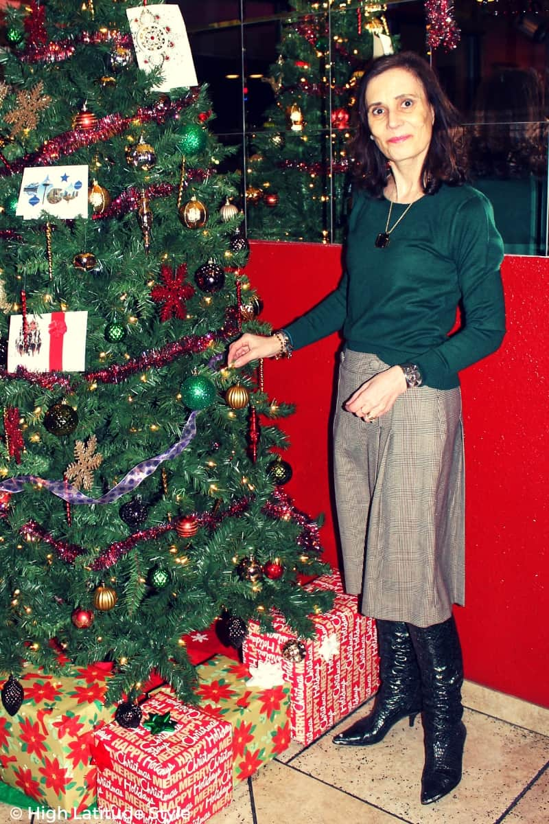 style blogger in hunter green top and boots, brown skirt with necklace in front of a decorated tree