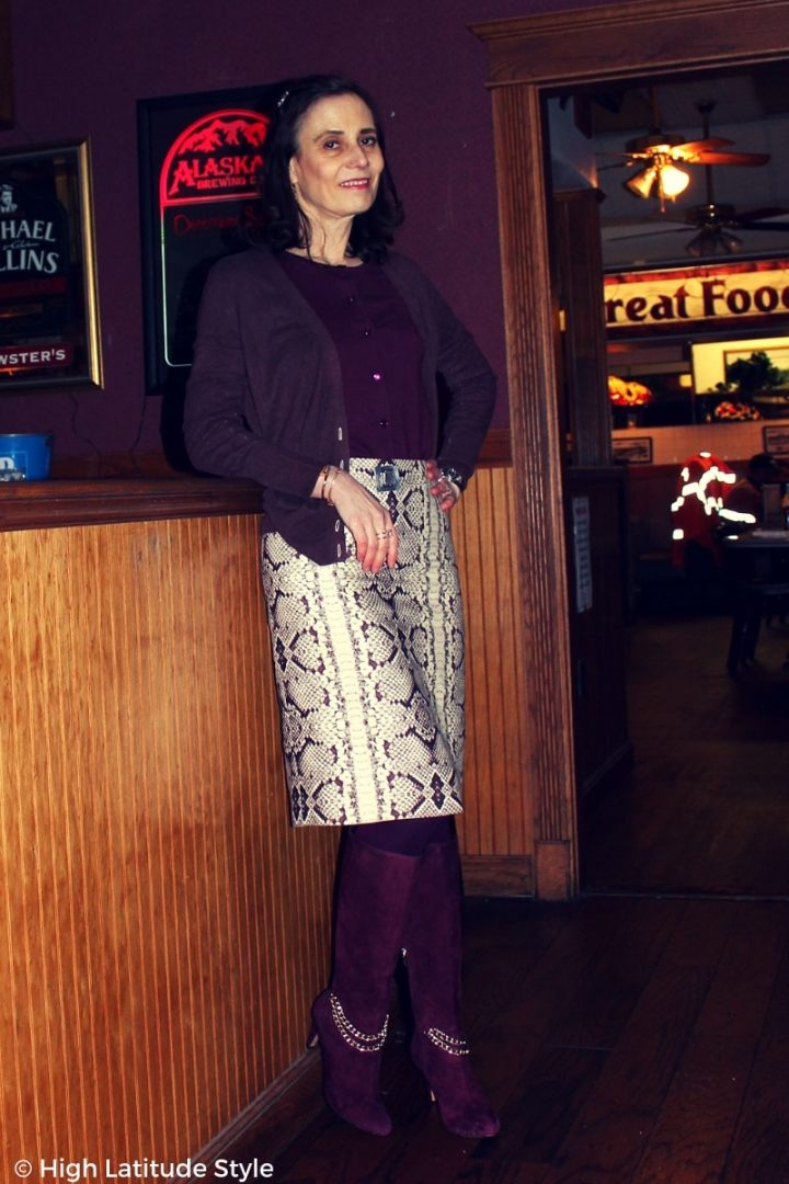#styleover50 blogger Nicole waiting at a lunch place in a snake print skirt, two cardigan and tall boots with holiday decoration in the back