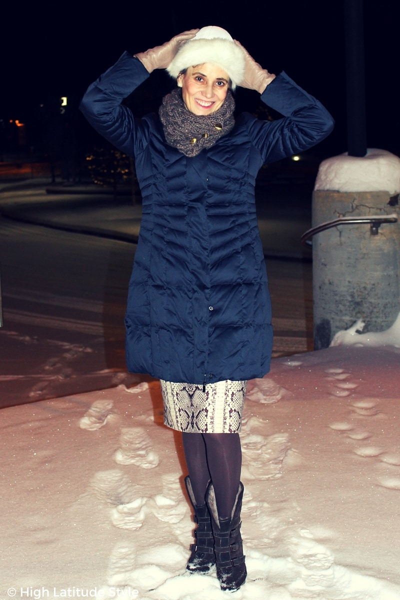 #winterfashion blogger Nicole in stylish slim winter puffer jacket psing with arms up in the dark