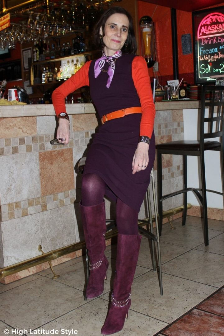 midlife woman in dress over sweater with belt and chain decorated boots
