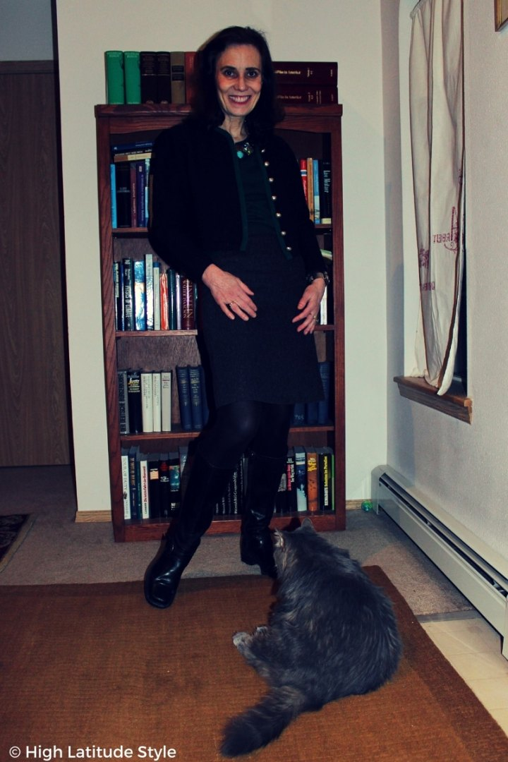 over 50 years old blogger in casual winter style with gray skirt, black boots, tights, jacket and huntergreen sweater with cat