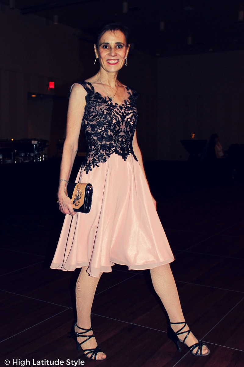 Nicole walking in strappy sandals in a lace chiffon gown carrying a fish pearl embellished wrist bag
