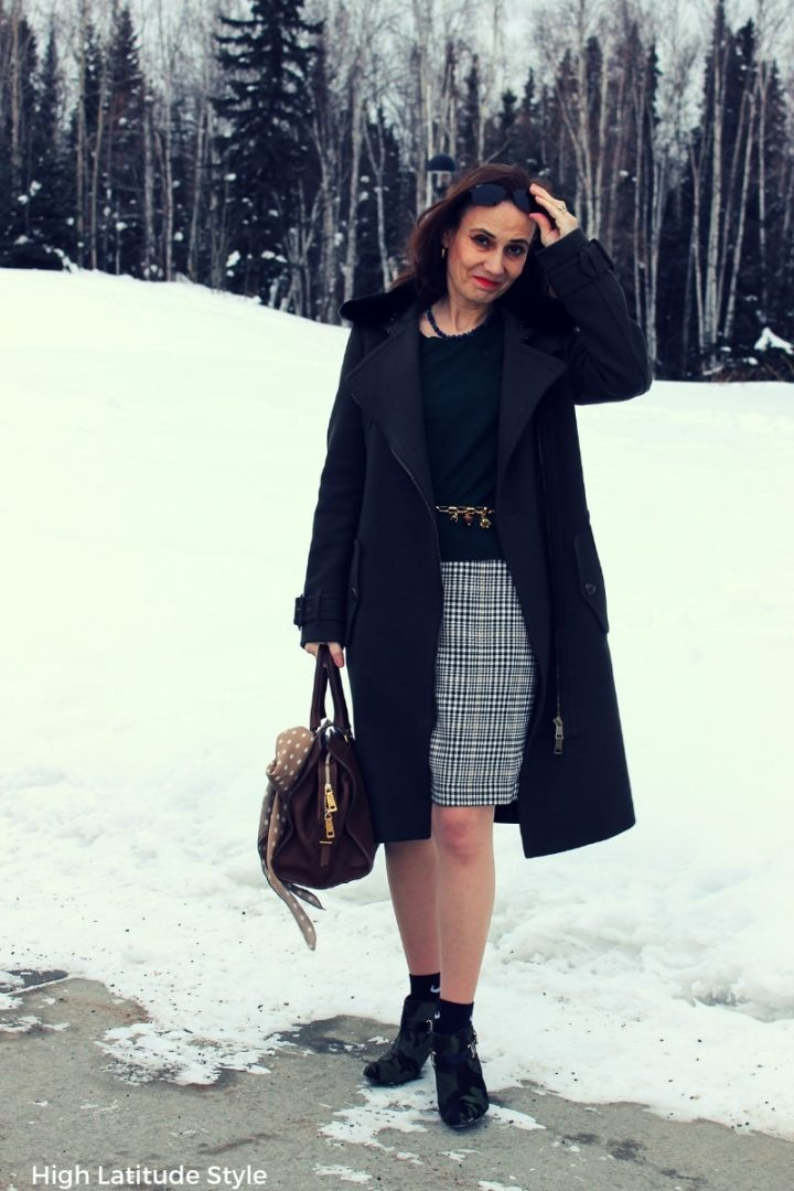 midlife woman in loden coat, pantyhose, socks, booties and skirt with sweater