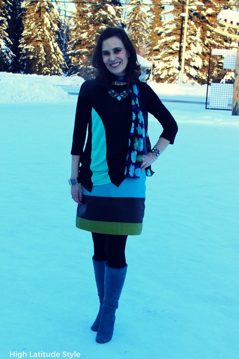 #styleover50 style blogger Nicole in an aqua, green and black work outfit with tall boots, assymmetric T-shirt and striped leather skirt