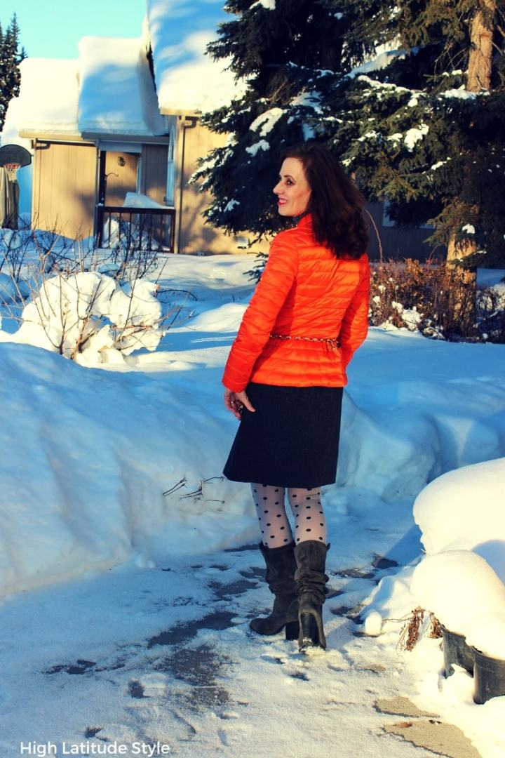 fashion blogger in orange jacket, gray skirt and boots in Alaska