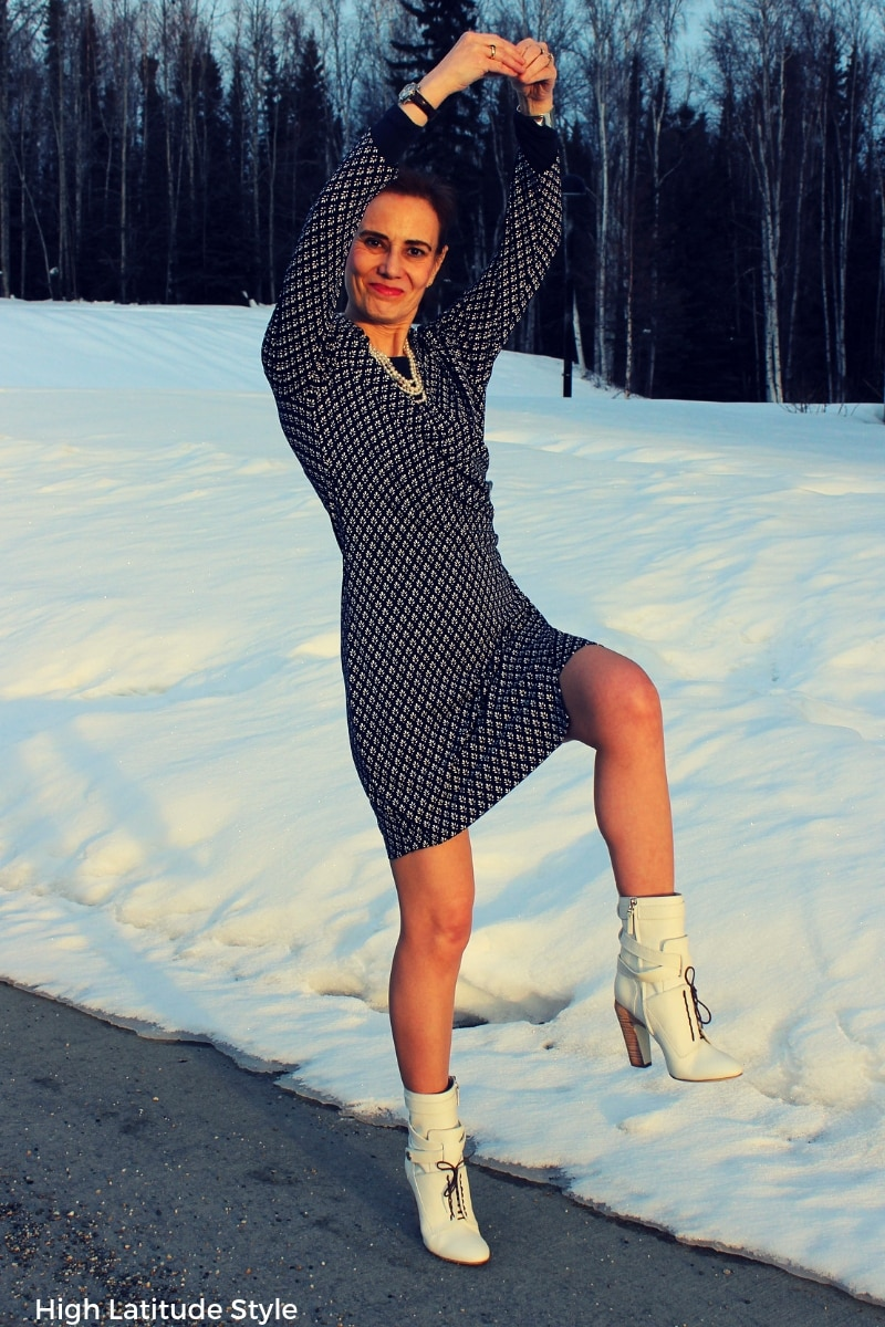 Fashion blogger in sophisticated faux wrap print dress with layering top and trendy white booties