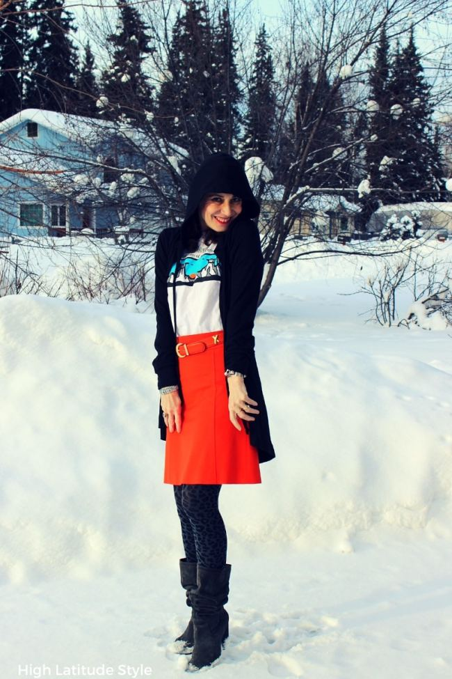 grassroot designer Tricia Tanaka cape.hoodie with orange skirt, T-shirt, loe tights and slouchy boots