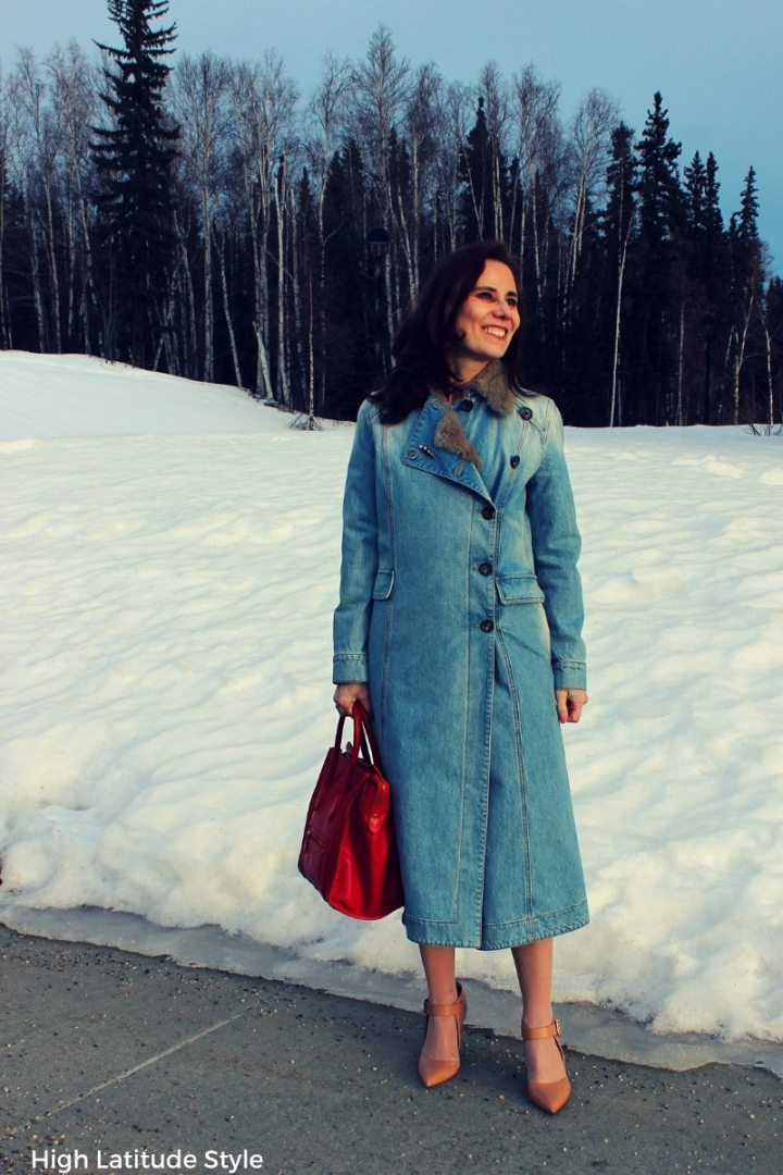 style blogger in denim coat, pantyhose and nude pumps with a red bag