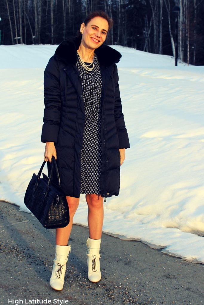 over 50 years old fashionista in wrap dress, pantyhose and downcoat with trendy booties