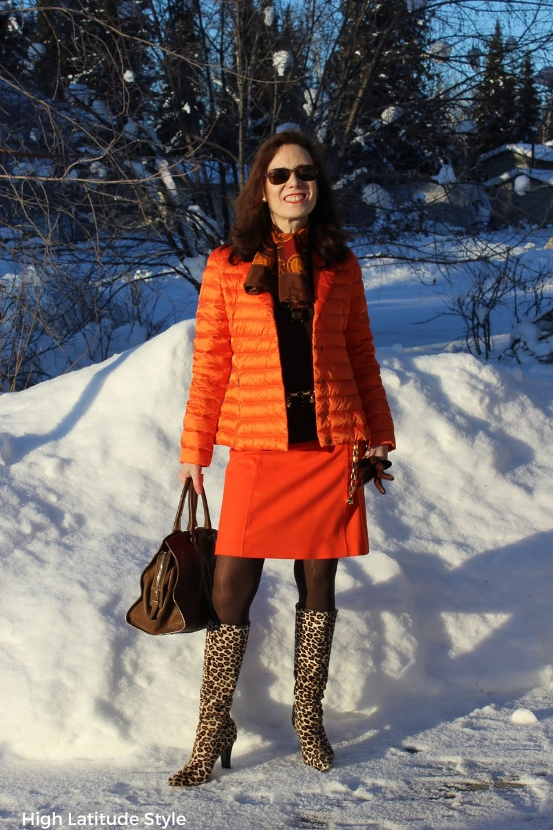 mature woman in leopard print boots and orange suit spring style in Alaska