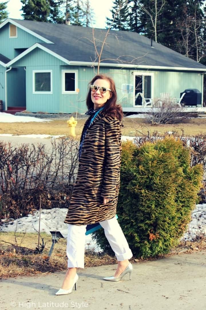 mature woman in zebra print coat and white denim pants