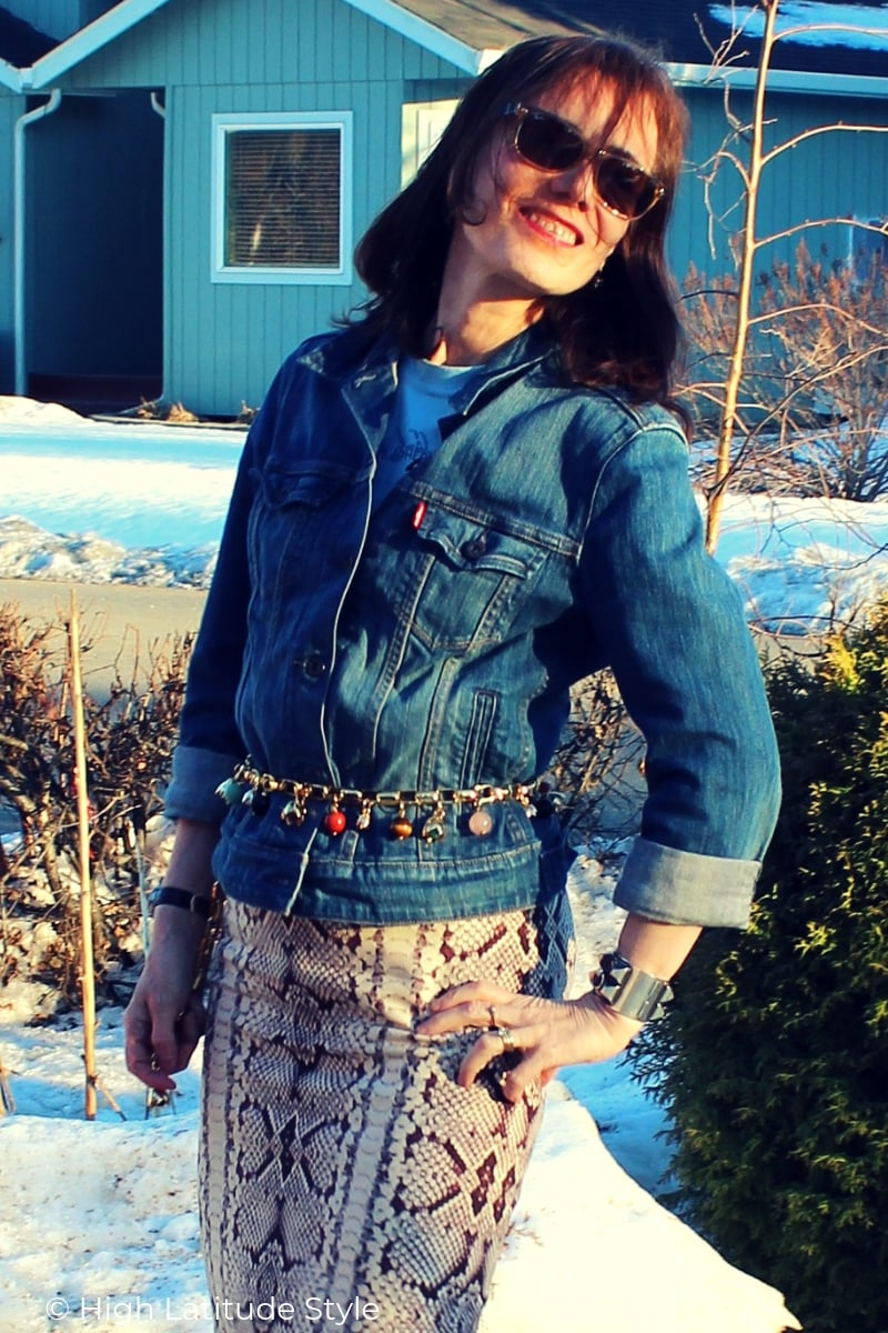 style blogger in T-shirt, jean jacket, statement belt, skirt, and sunnies