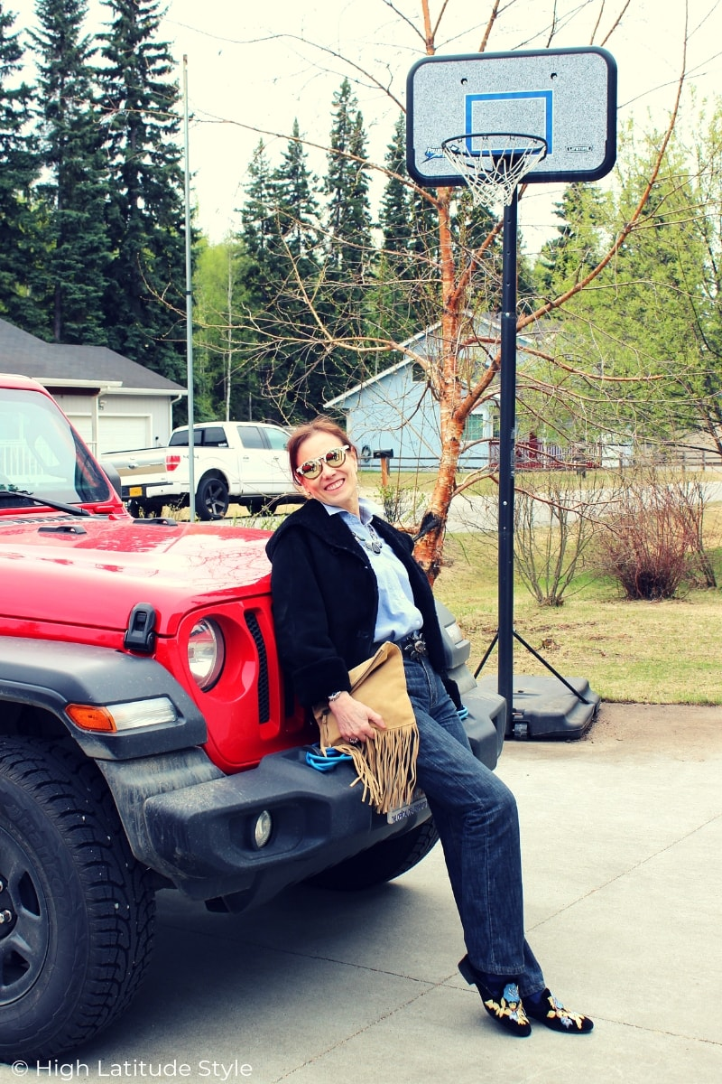 lady sitting on a Jeep Wrangler in a preppy casual weekend look with boyfriends jeans, mules, button-down shirt and shearling coat