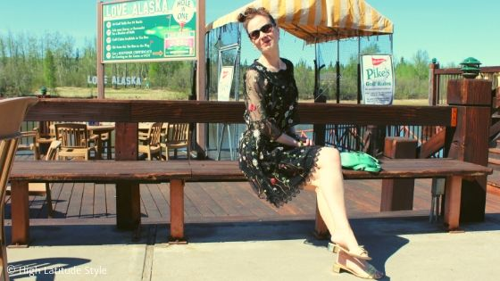 midlife blogger sitting on the bench of a resort place in flower embroidered tunic
