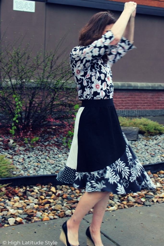 mature woman twirling in mixed print trend outfit