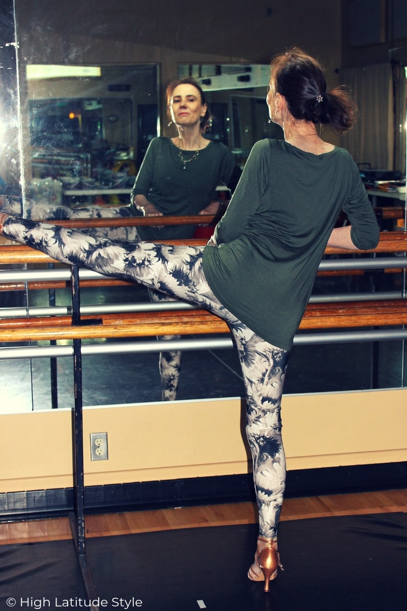mature dancer stretching at a bar wearing leggings and a long boat-neck tee cut for women over 40