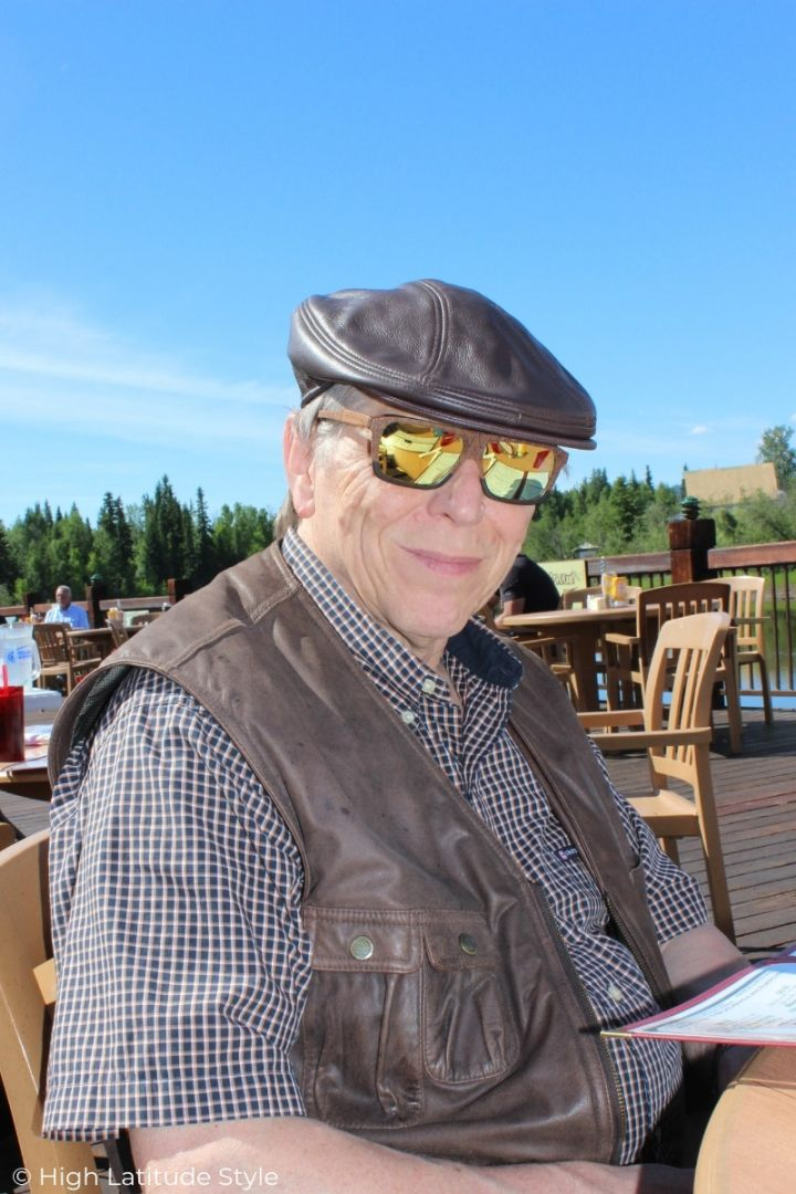 midlife men wearing a leather ivy cap and leather vest with plaid shirt and sunglasses