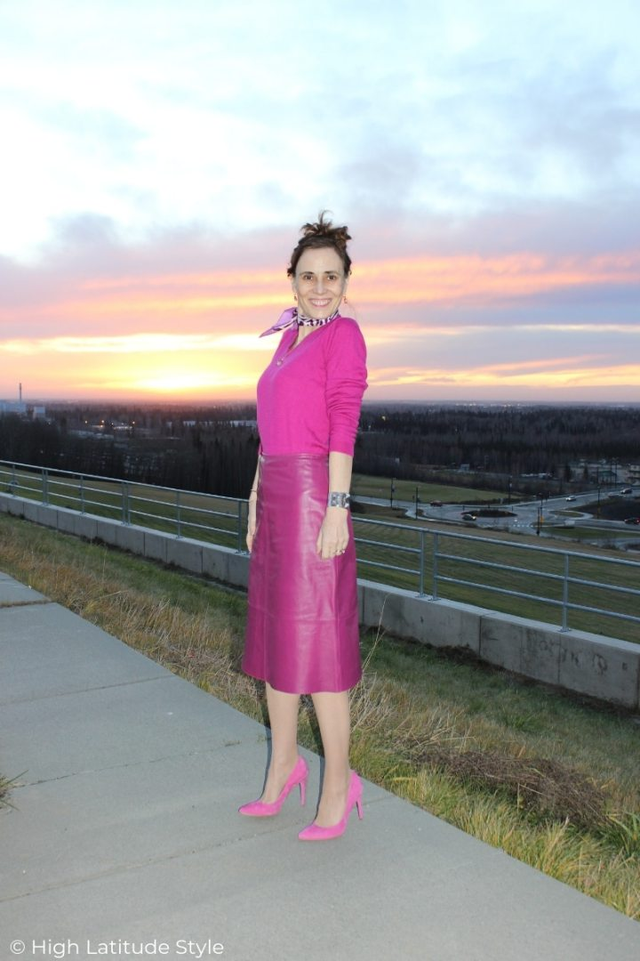 over 50 years old fashion blogger in pink leather skirt, top and pumps at a viewpoint in Alaska