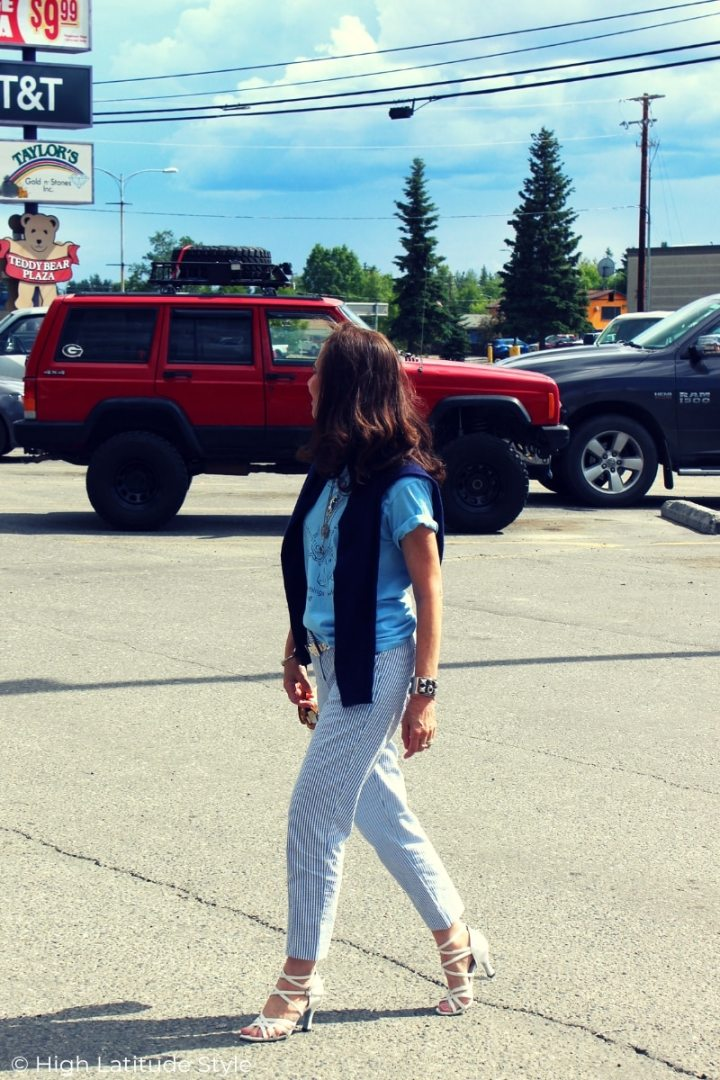 Style blogger Nicole walking thru a parking lot in a graphic T, seesuckers and white strappy heels