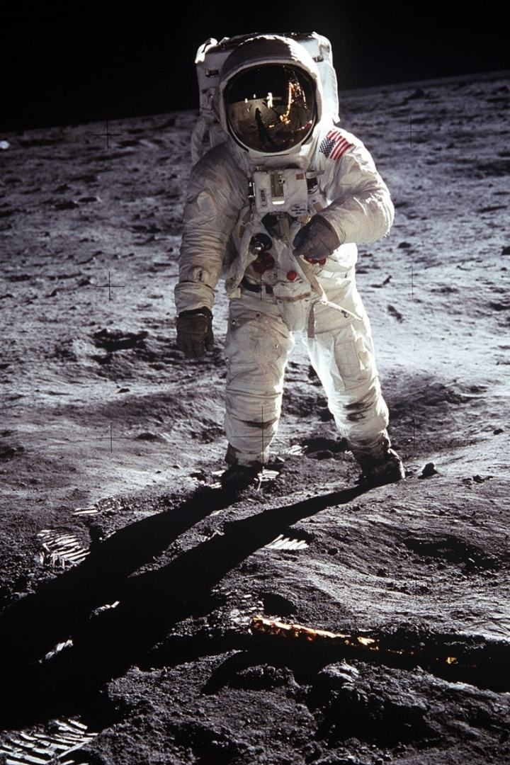 astronaut in a space suit standing on the moon with the lunar mobile mirrored in the helmet