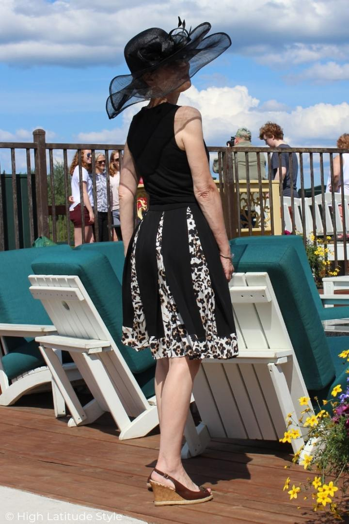 mature woman in fit-and-flare black dress with leopard print hem and insets