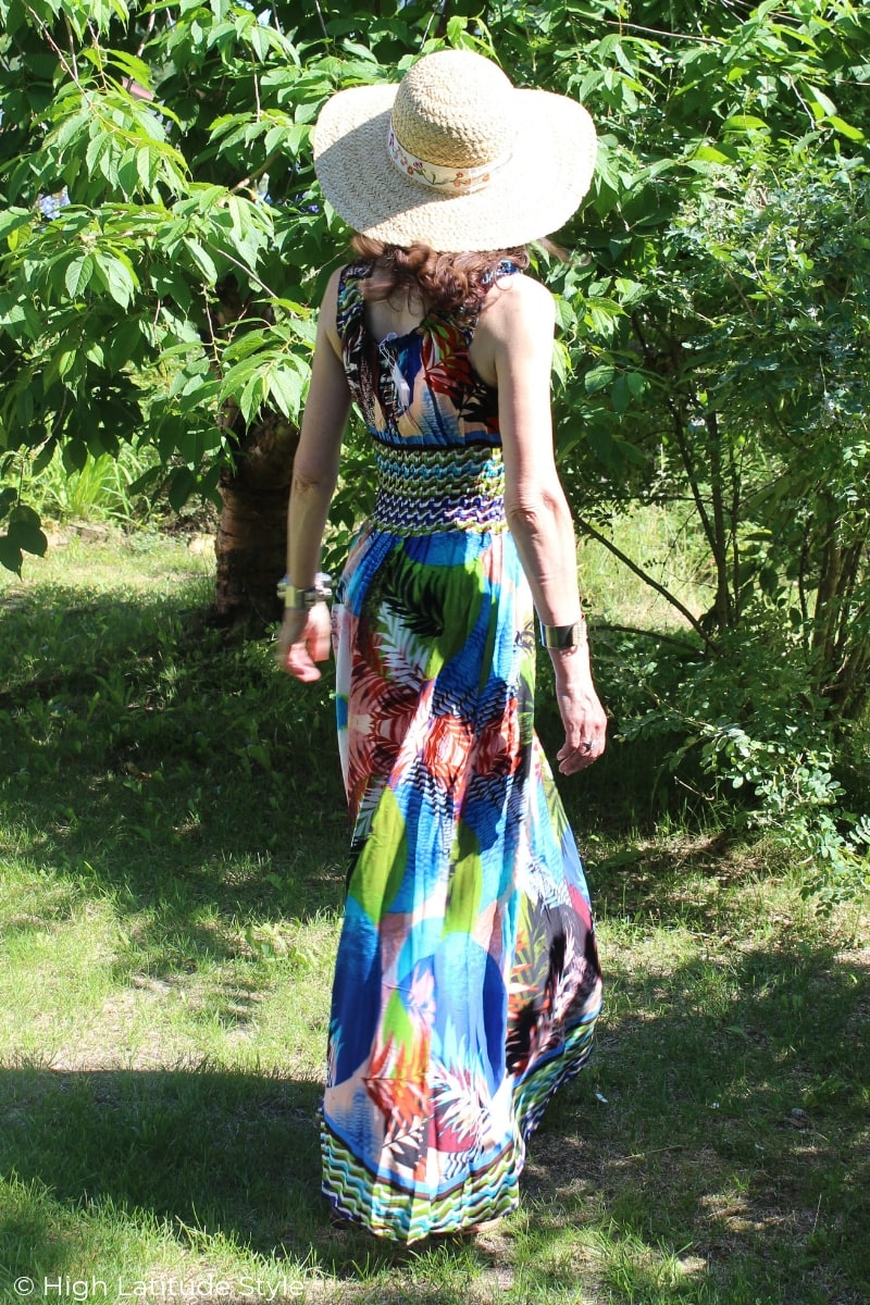 woman in straw hat and long abstract multi color print dress with stripes at the hem and waist