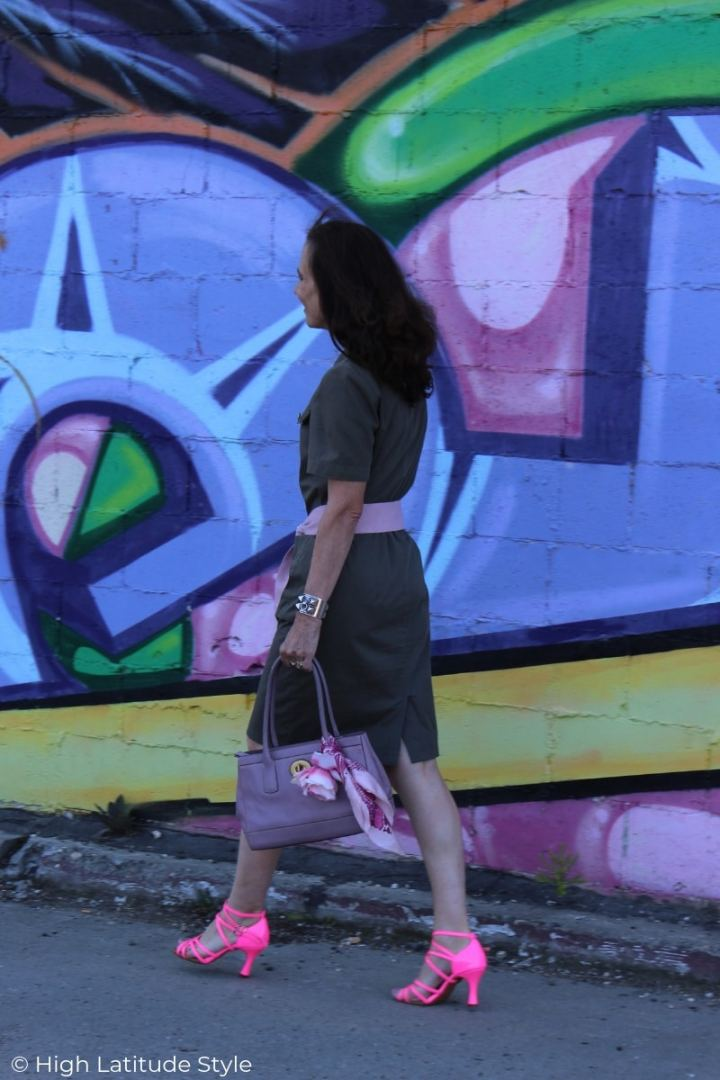 over 50 years old style blogger in military inspired dress, dance shoes walking along a mural