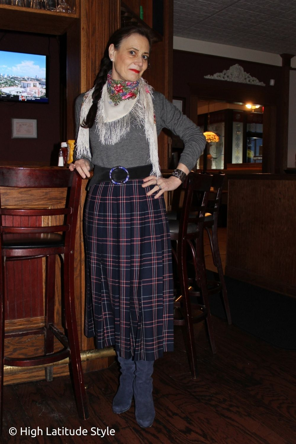 stylist in pleated multi-color skirt, floral wool scarf turtleneck and boots