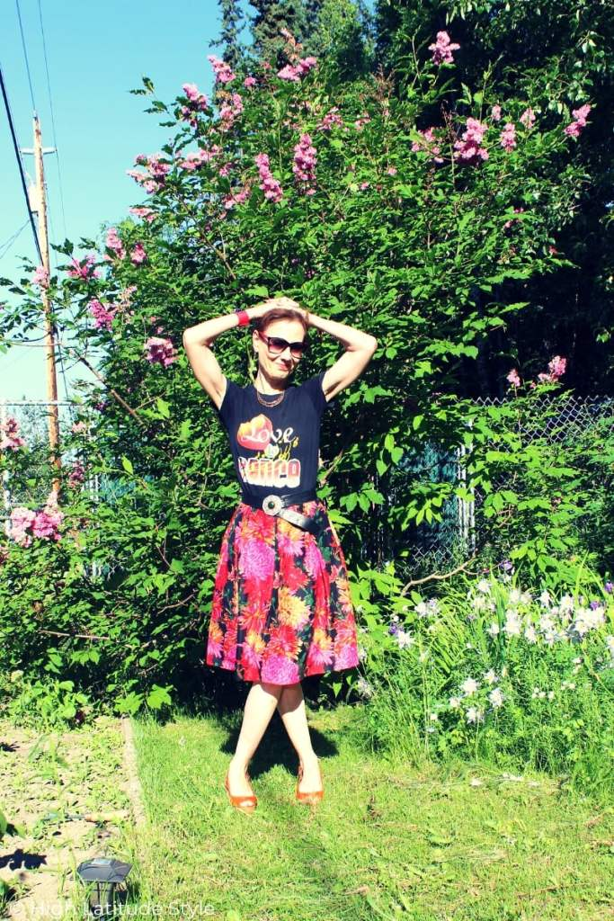 over 50 years old fashion blogger in floral skirt and graphic T under blue sky