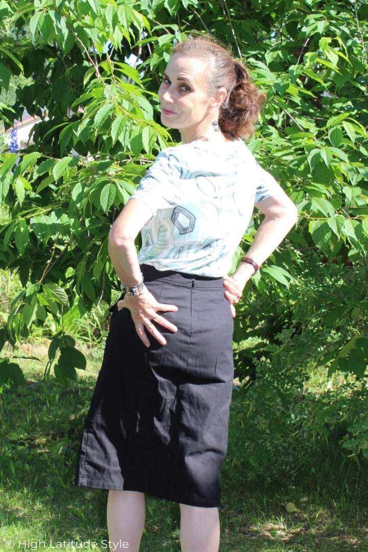 woman looking backwards in a black knee length slim skirt and print blouse