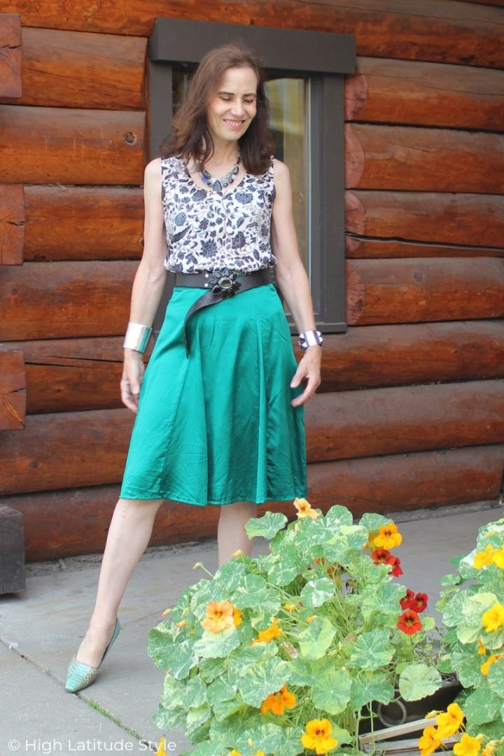 midlife fashion blogger in flowy skirt, printed top with bold bangles and belt