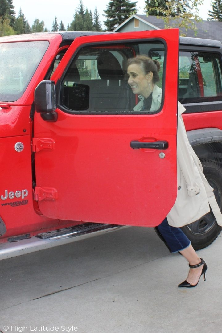 mature woman in trench, heels and jeans getting into a Jeep