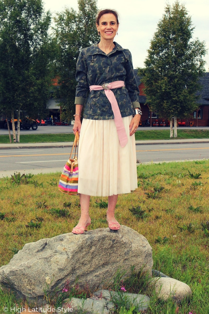 over 50 years old fashion blogger standing on a rock in mules, midi skirt and military inspired jacket