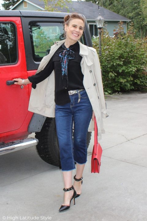 midlife woman in Casual Friday outfit with blue jeans, black blouse, floral bow, taupe coat, red bag and black heels
