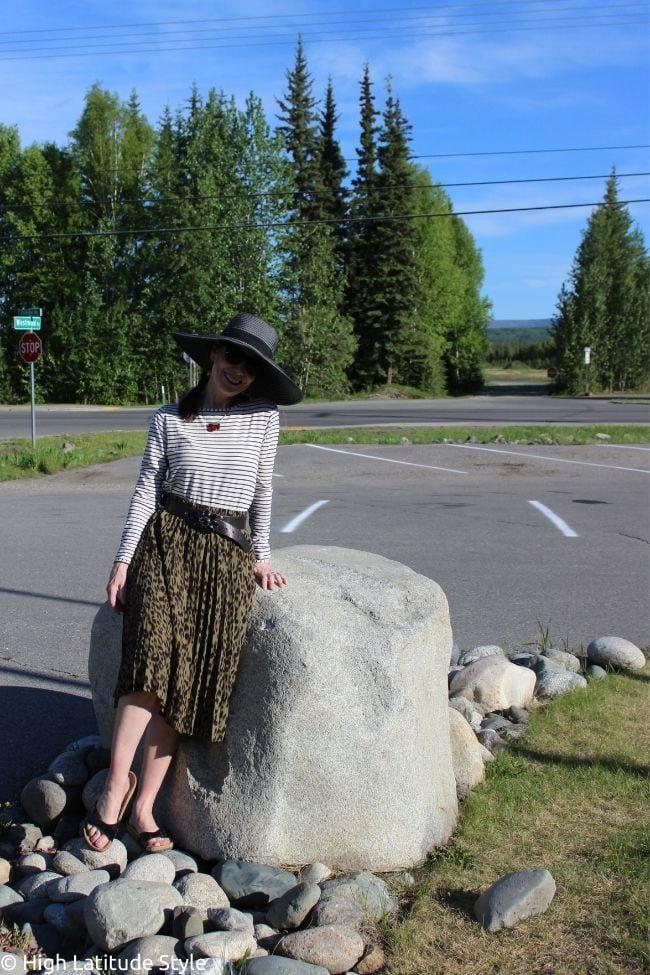 influencer in July look of leopard print skirt, striped shirt, hat, Birkenstocks