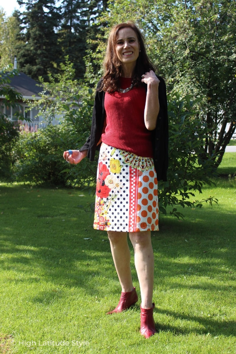 midlife woman in printed skirt, booties, top and jacket work outfit