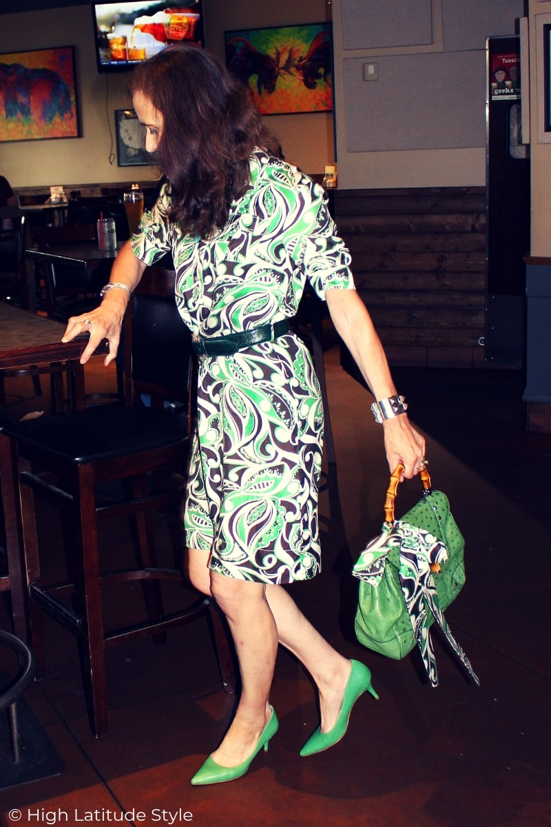 midlife woman in printed summer dress with accessories and matching bow on her purse