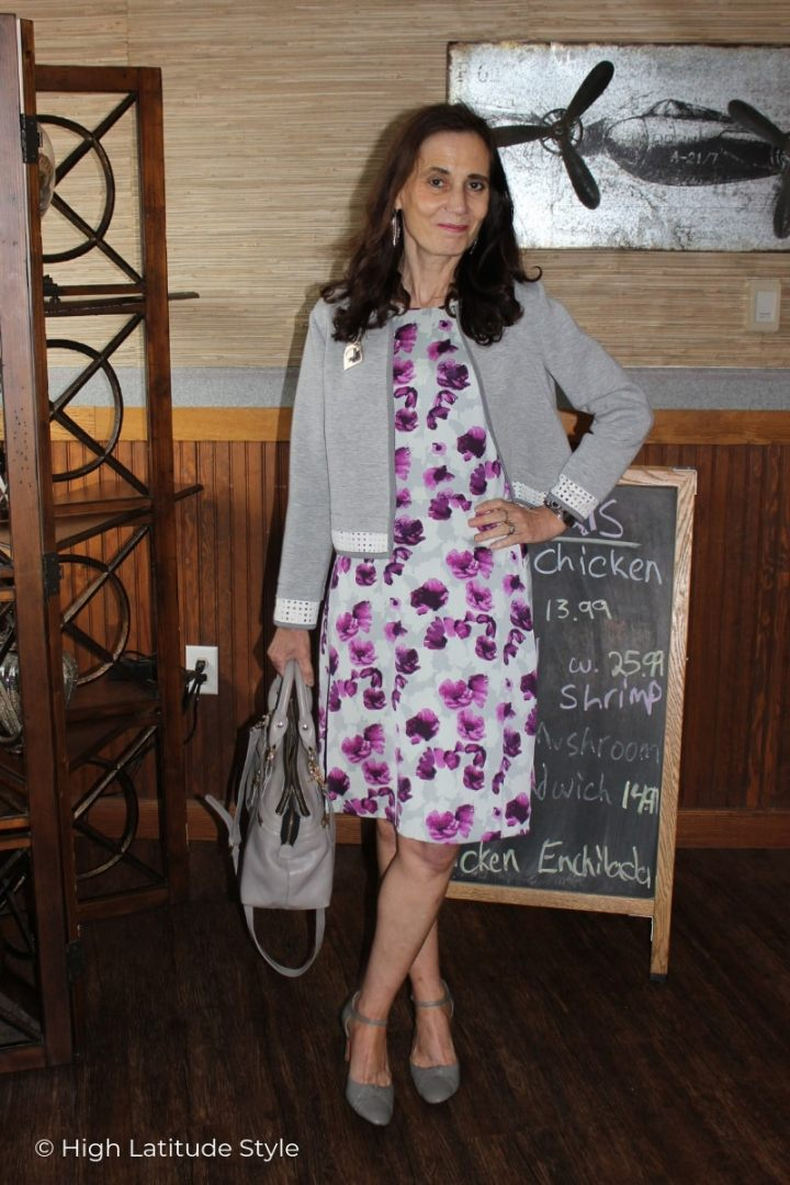 Nicole of High Latitude Style in abtract floral print work dress, cropped scuba jacket and ankle strap pumps