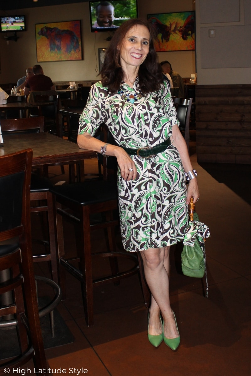 style book author in summer work outfit of an abstract print dress with color matched purse, shoes and belt