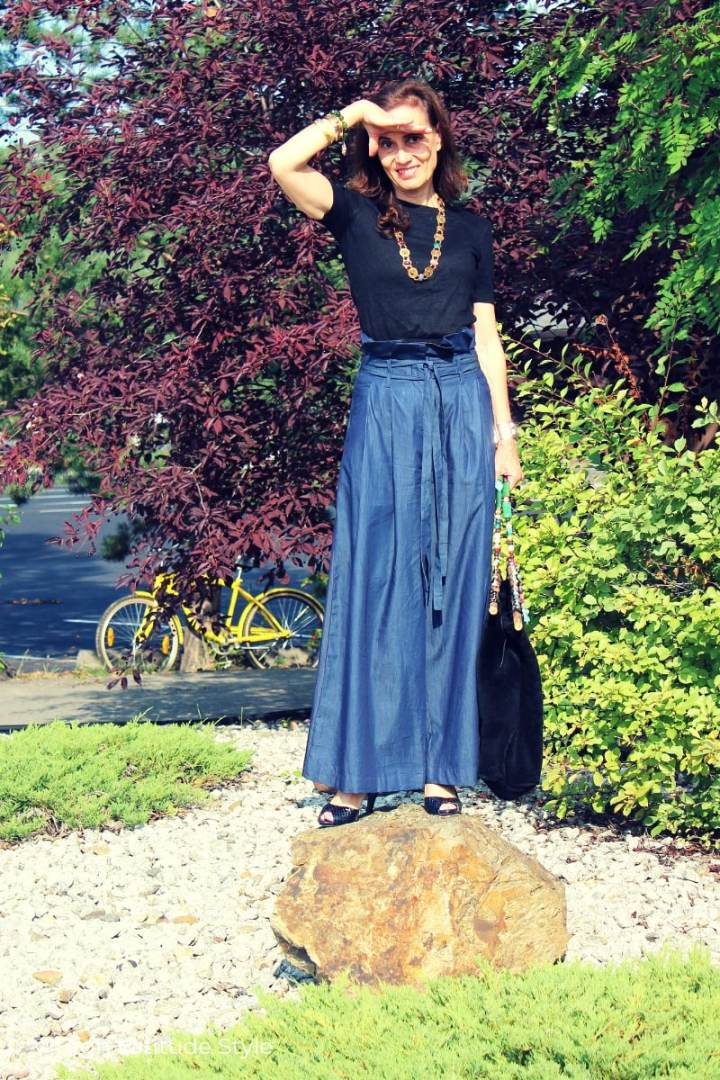 Alaskan style blogger in casual outfit with long wide pants, knit sweater, gemstone necklace, pumps and excentric bag