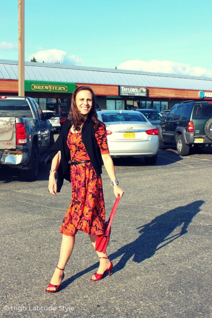 over 50 years old fashion blogger walking in an orange print dress and red shoes in a mall