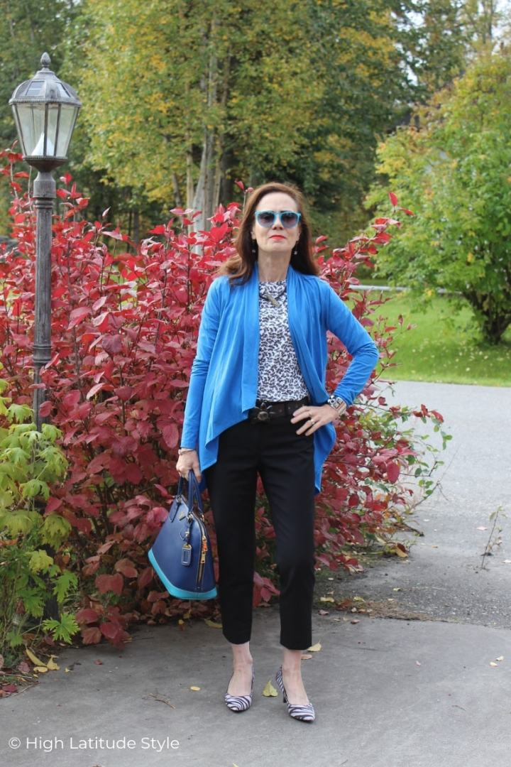 over 50 years old blogger in blue jacket, sunglasses and bag with BW top and dark pants