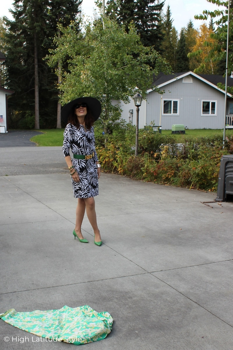 Alaskan midlife woman standing on a driveway in sun protective hat, dress with scarf