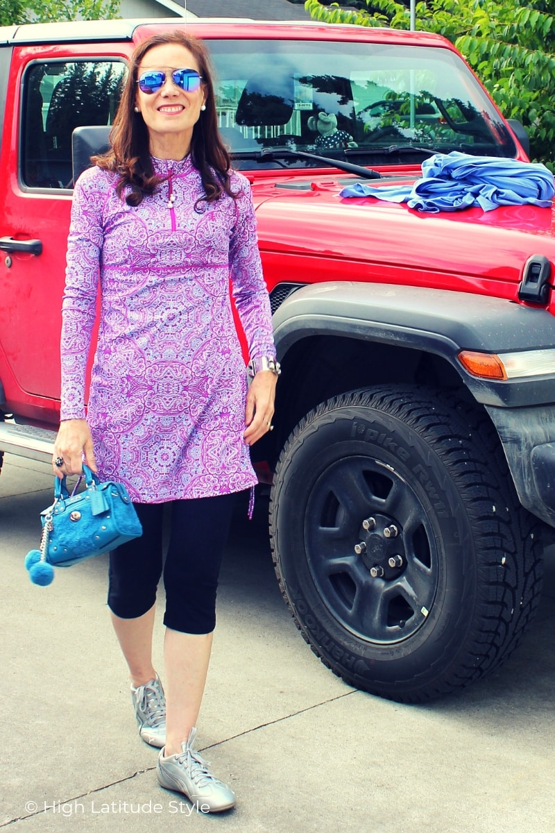 midlife blogger in casual UPF clothing in front of a car