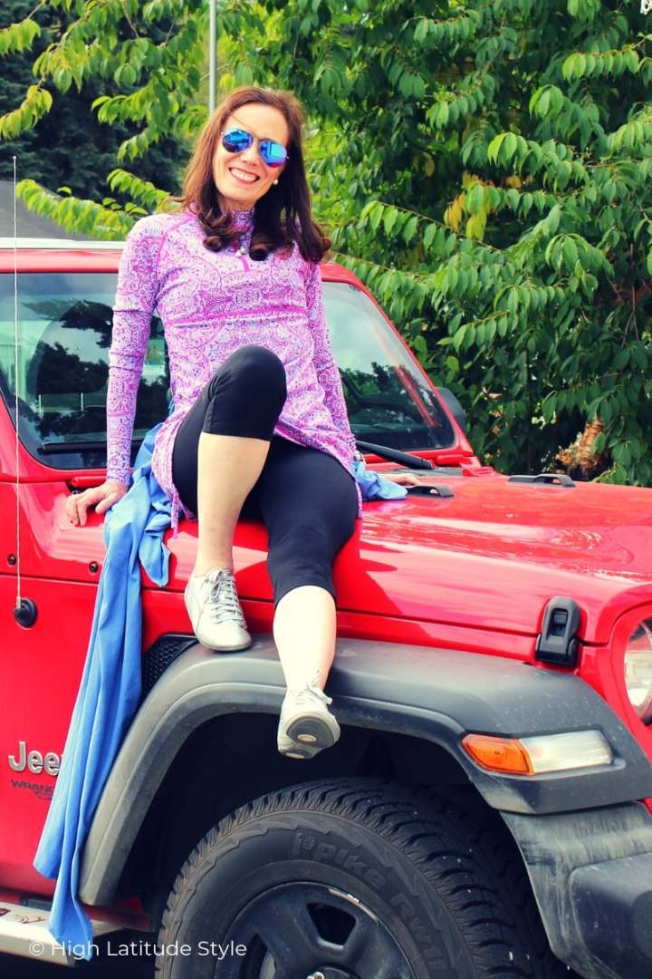 over 50 years old blogger sitting on a Jeep in sunprotection coolibar swimwear