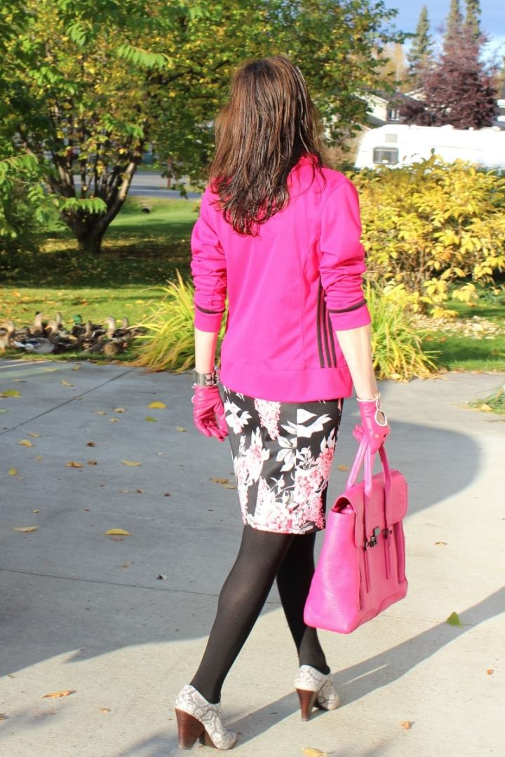 fashion blogger walking in tights, floral sheath and pink Adidas jacket