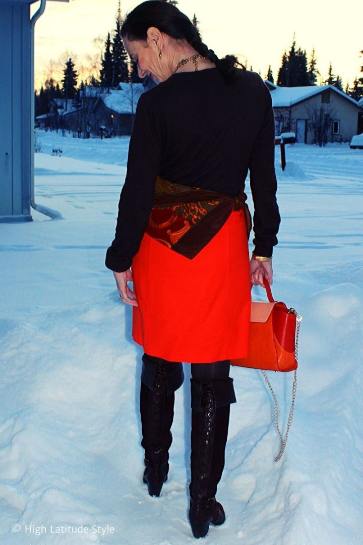 Alaskan over 50 years old woman in orange skirt, printed scarf, brown sweater, tights and boots with orange bag