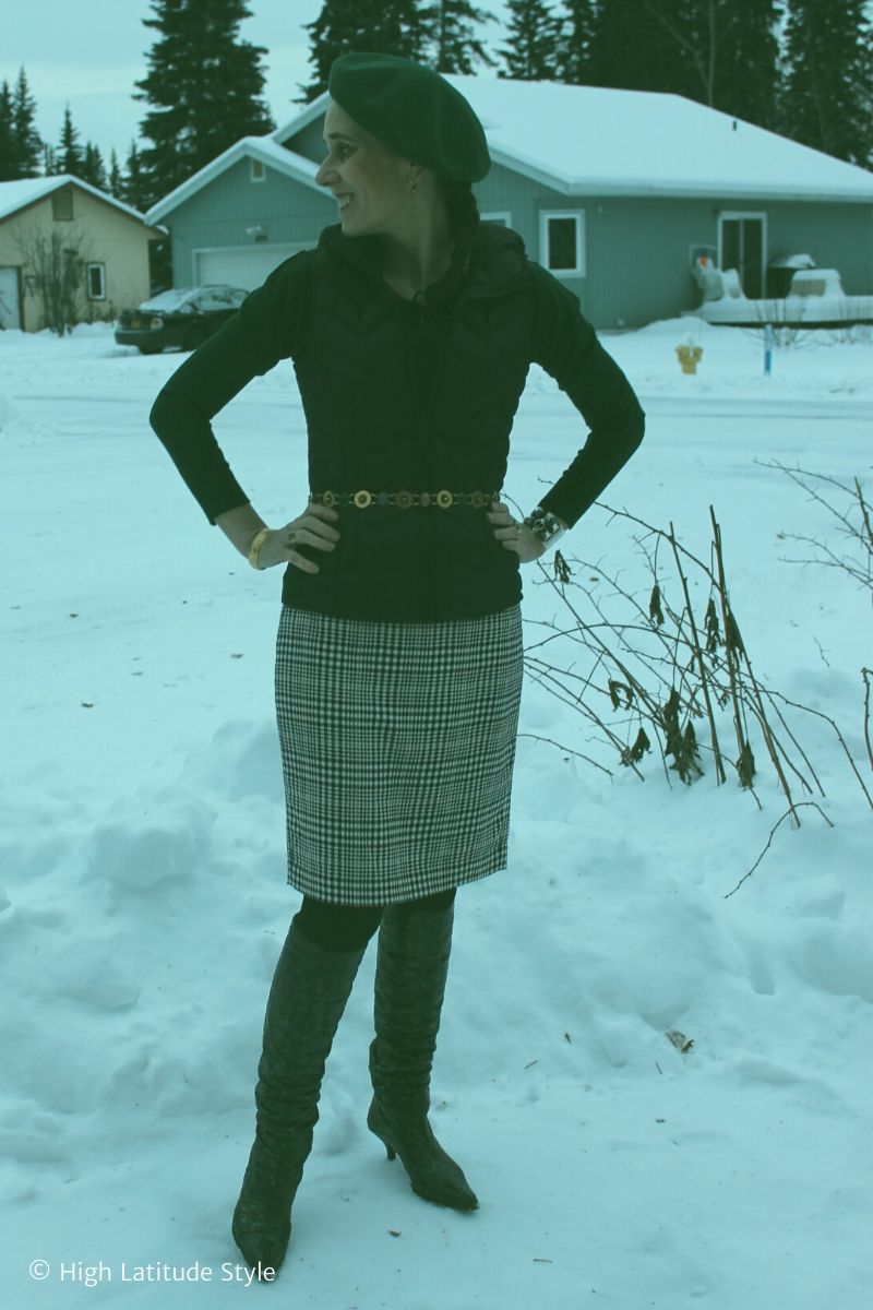 Alaskan woman in business casual winter look with houndstooth skirt, tights, hunter green sweater, beret and boots