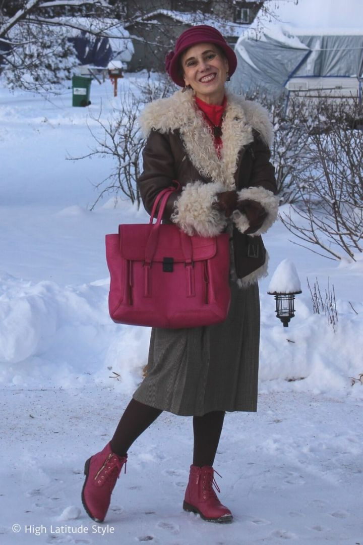 stylist walking thru the snow in pleated midi skirt, motorcycle jacket, hat, gloves, pink boots